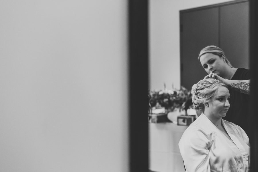 black and white photo of bride getting her hair done