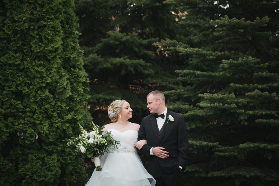 bride and groom standing with evergreens