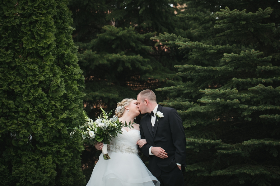 bride and groom kissing in front of evergreens at club at corazon