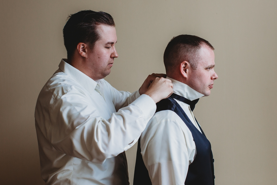 best man helping groom with bow tie at the Club at Corazon