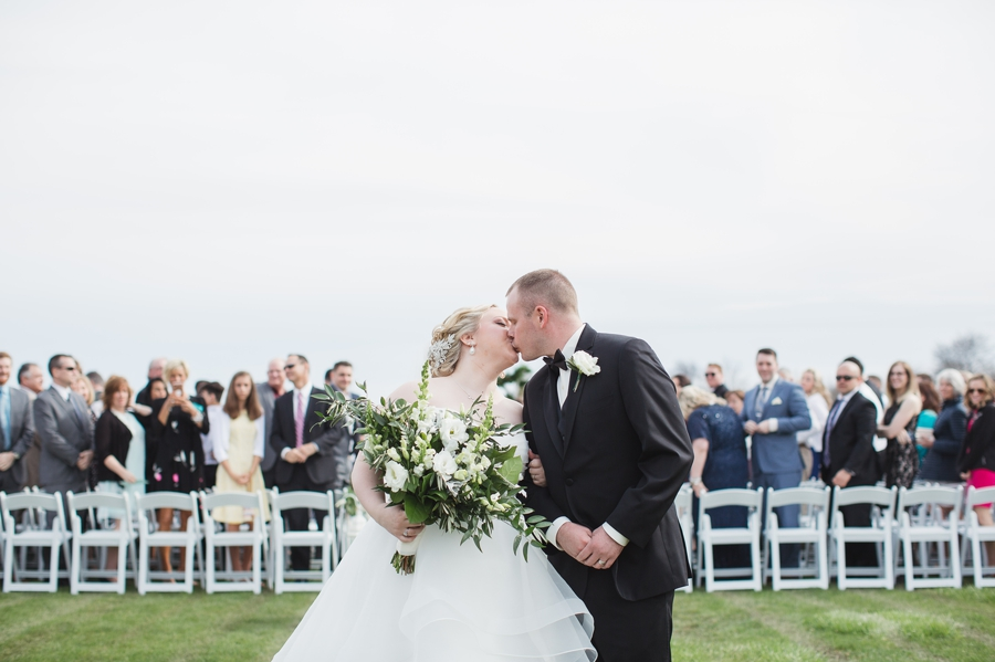 married couple kissing with guests in background