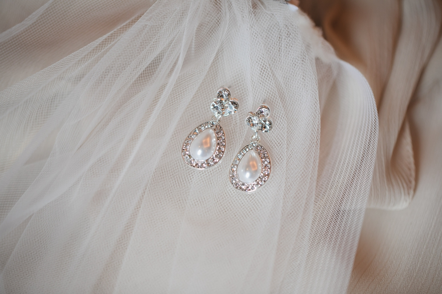 brides earrings laying on veil