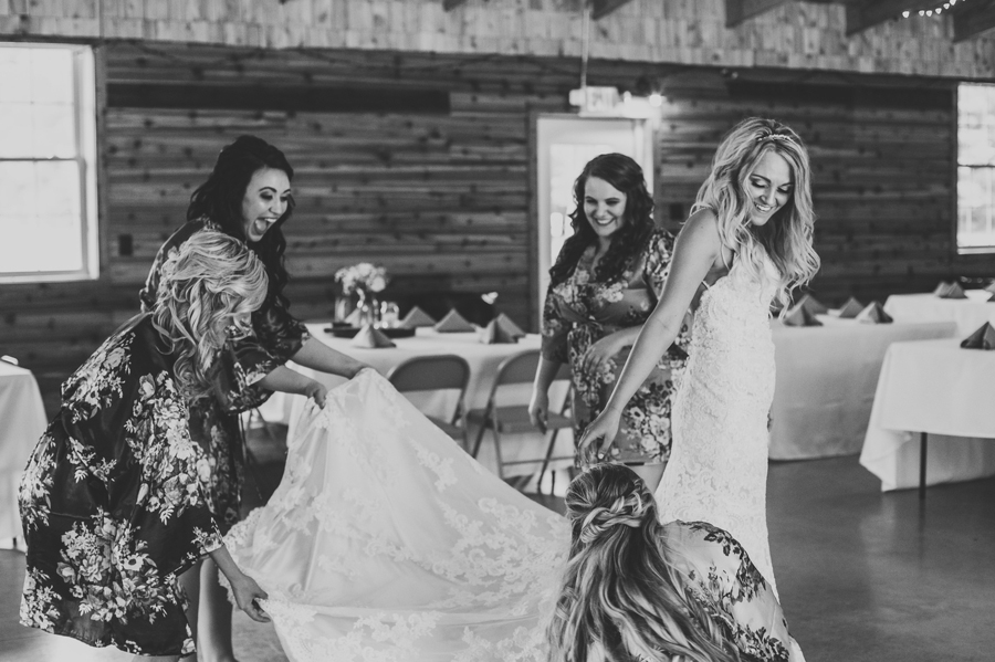 black and white photo of bridesmaids helping bride get into wedding gown