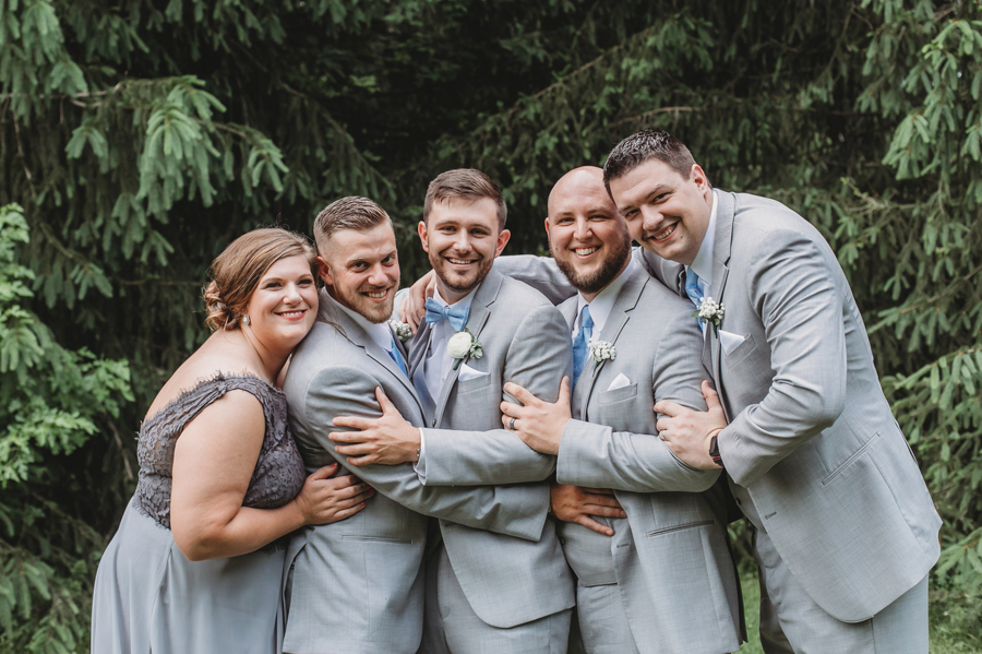 groom being hugged by wedding party
