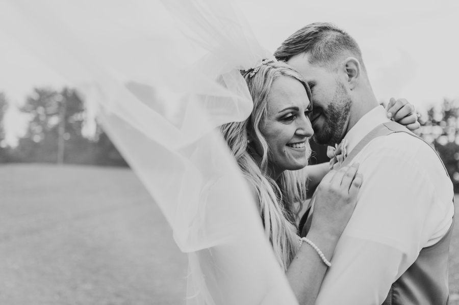 black and white photo of couple with veil
