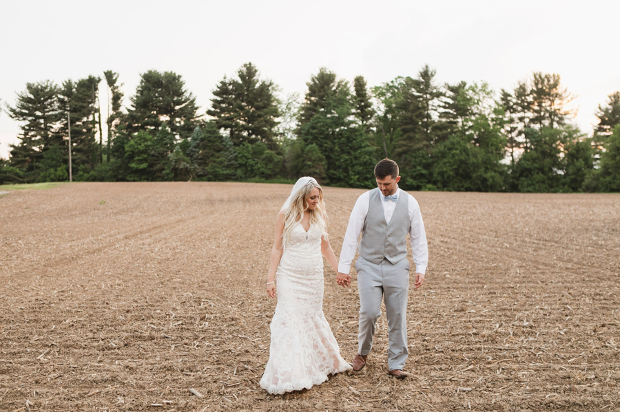 married couple holding hands walking out of field
