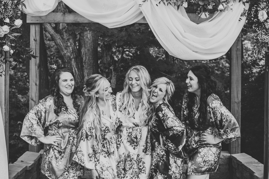 black and white candid photo of bride with bridesmaids